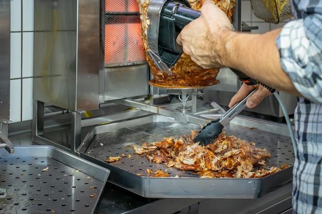 Il doner kebab o gyros su un piatto con patatine fritte viene preparato nel ristorante