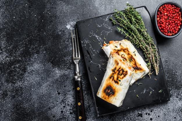 Rotolo di doner kebab in un lavash con carne di pollo e manzo. fondo in legno nero. vista dall'alto. copia spazio.
