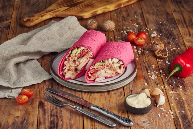 Doner kebab (shawarma o doner wrap). pollo alla griglia su lavash con pomodori, insalata verde e peperoni sul tavolo di legno