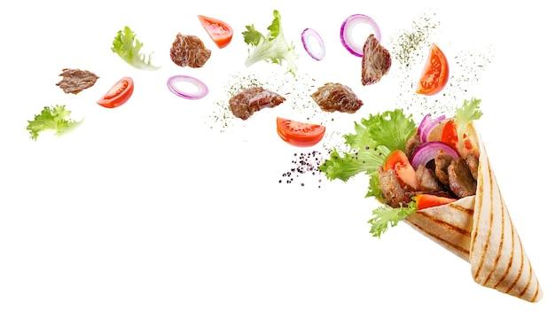 Doner kebab o shawarma con ingredienti fluttuanti nell'aria: carne di manzo, lattuga, cipolla, pomodori, spezie.