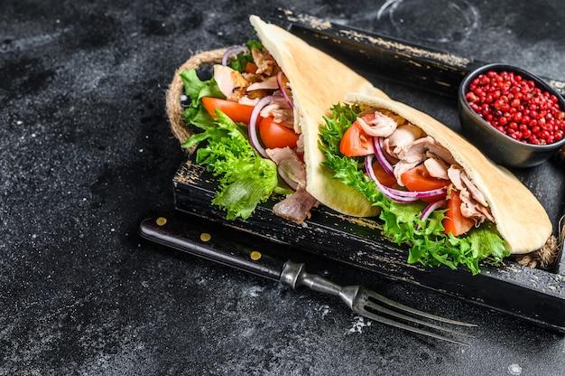 Döner kebab con carne di pollo alla griglia e verdure in pane pita su un vassoio di legno