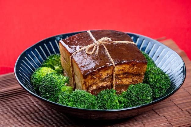 Dong po rou dongpo carne di maiale in una bella piastra blu con broccoli verdi tradizionali vegetali cibo festivo per il capodanno cinese pasto cucina primi piani