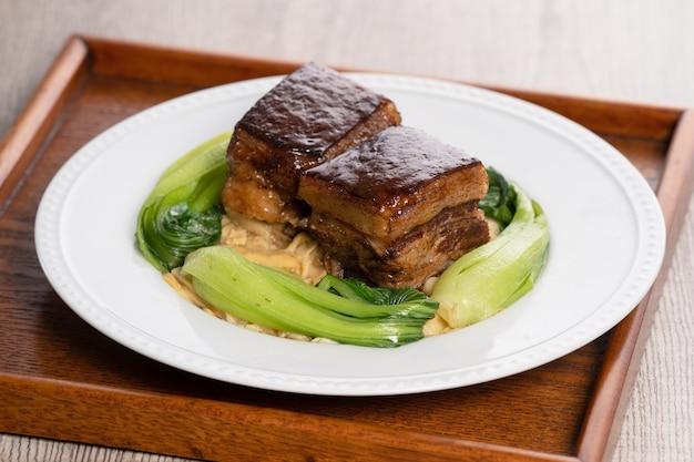 Dong po rou (carne di maiale dongpo) in un bel piatto blu con verdure broccoli verdi, cibo tradizionale festivo.