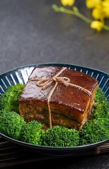 Dong po rou (carne di maiale dongpo) in un bel piatto blu con verdure broccoli verdi, cibo tradizionale festivo
