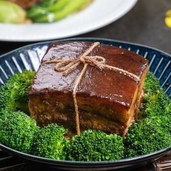 Dong po rou (carne di maiale dongpo) in un bel piatto blu con verdure broccoli verdi
