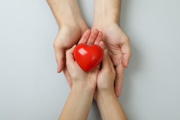 Concetto di donatore con le mani che tengono il cuore rosso su sfondo bianco
