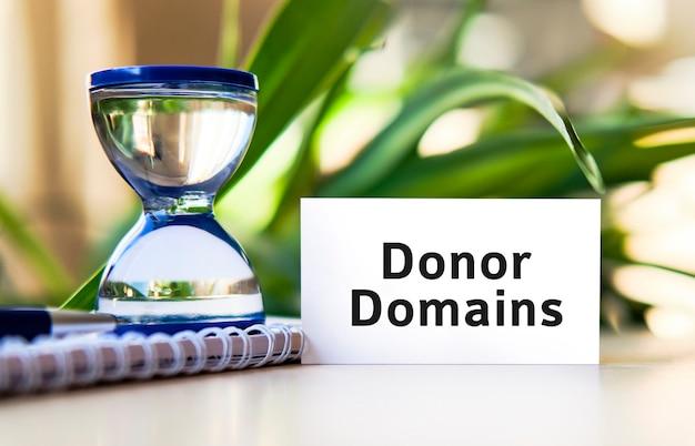 Domini donatori per sito web seo - testo di concetto di affari su un taccuino bianco e un orologio a clessidra, foglie verdi di fiori