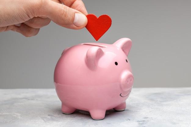 Donatore. un uomo tiene in mano un cuore rosso e va al salvadanaio come donazione.