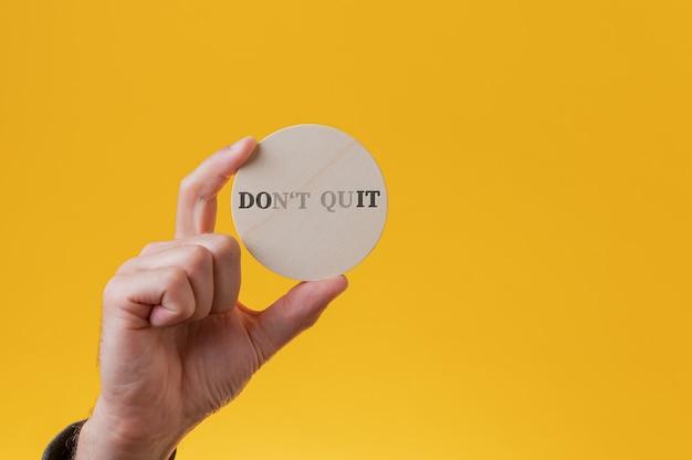 Non smettere di firmare scritto su un cerchio di legno tagliato con alcune lettere che svaniscono per leggere un segno fallo.