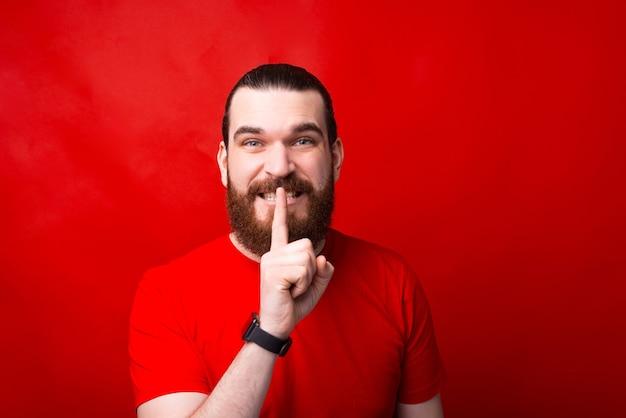 Non dirlo a nessuno, questo è segreto, foto di un uomo barbuto che fa un gesto di shh