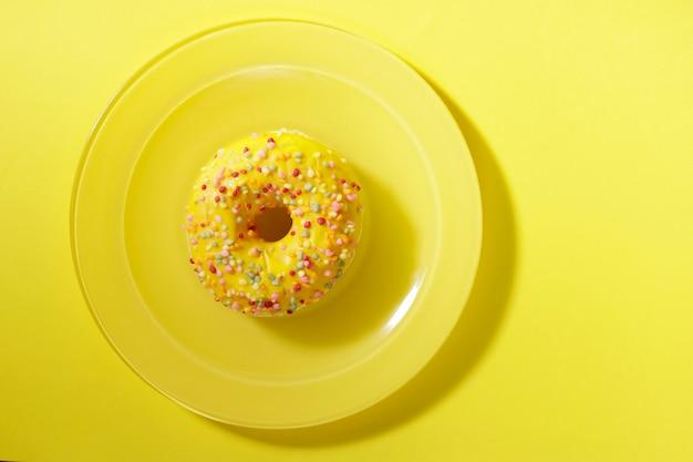Ciambella decorata con scintille colorate su un piatto giallo su sfondo giallo