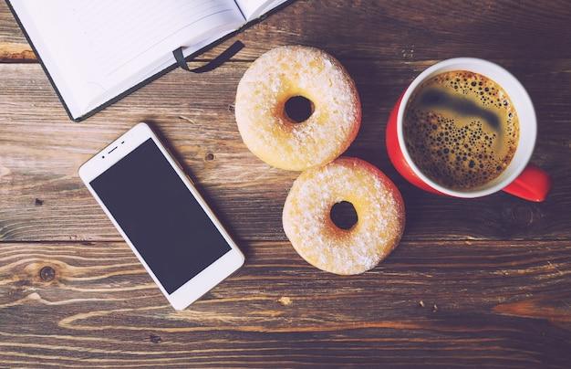Ciambelle e caffè sdraiati su fondo in legno rustico con blocco note aperto e vista dall'alto del telefono cellulare
