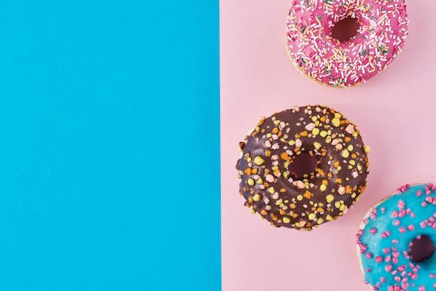 Ciambelle su rosa pastello e blu. composizione di cibo creativo minimalismo. stile piatto laico