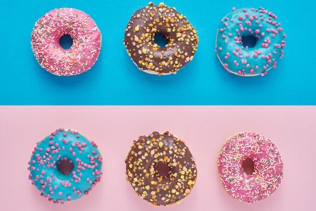 Ciambelle su rosa pastello. composizione di cibo creativo minimalismo. stile piatto laico