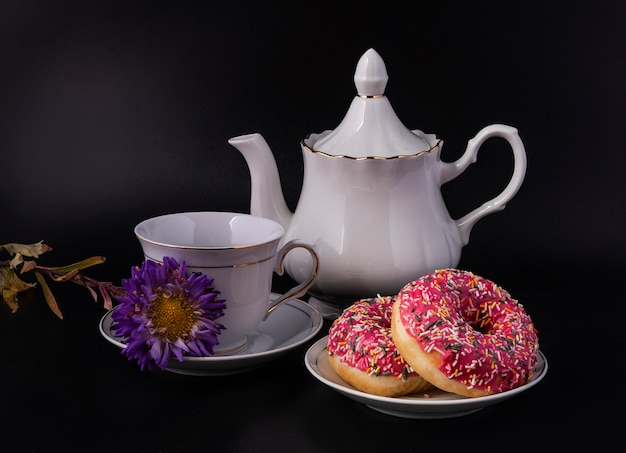 Ciambelle e un set da tè per la colazione mattutina su sfondo nero.