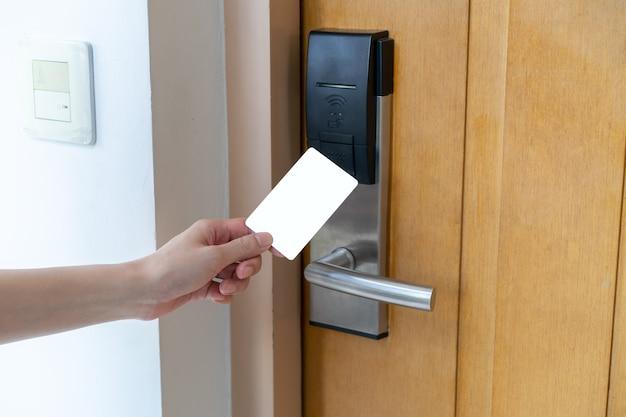 Controllo di accesso alla porta - mano della donna che tiene la chiave magnetica bianca per bloccare e sbloccare la porta. serratura digitale.