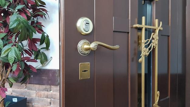 Maniglia della porta, serratura della porta. la porta blindata metallica d'ingresso è semiaperta alla casa. aprendo la porta. benvenuto concetto di privacy. design moderno degli interni.
