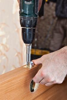Installazione della porta, montare le manopole delle porte chiuse, carpentiere nell'installazione della serratura della porta interna in legno.