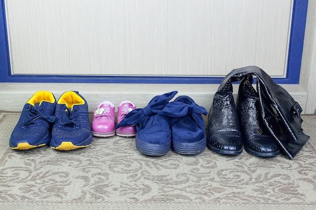 Zerbino con parola benvenuto e scarpe sul pavimento, vista dall'alto.