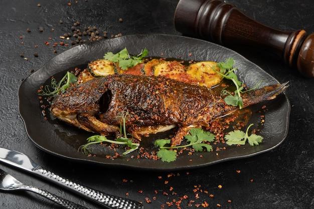 Dorada con zucchine fritte. piatto caldo di pesce di mare e verdure al forno con microgreens e spezie su un bel piatto nero