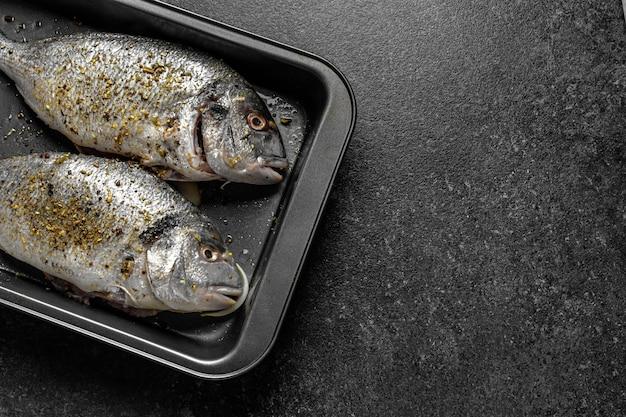 Dorado pesce crudo in spezie su una teglia copia spazio