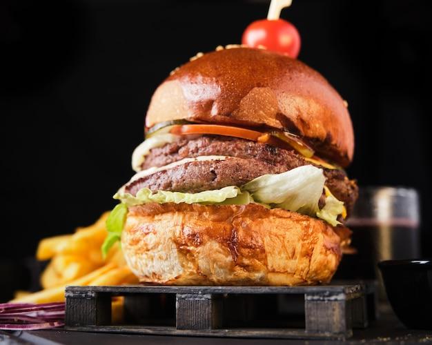 Doppio cheeseburger di manzo con patatine fritte americane su uno sfondo scuro.