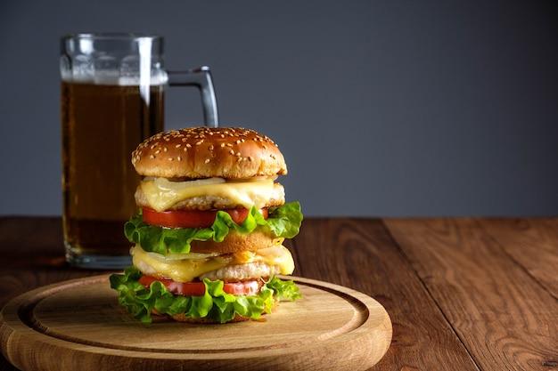 Doppio hamburger con formaggio, insalata, cotolette e bicchiere di birra su fondo in legno