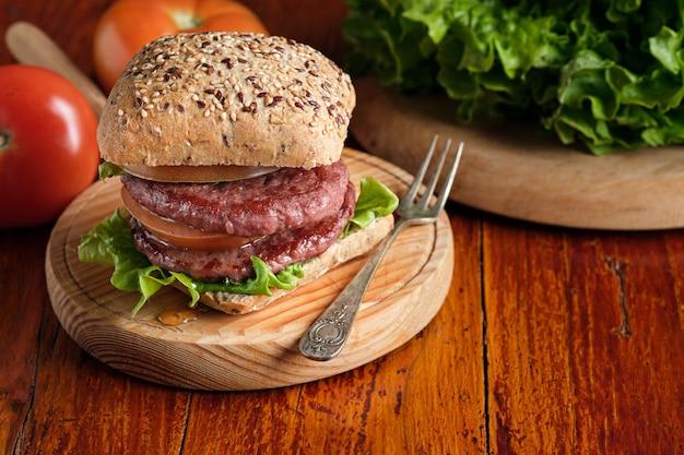 Doppio hamburger con pomodoro e lattuga su base rustica in legno