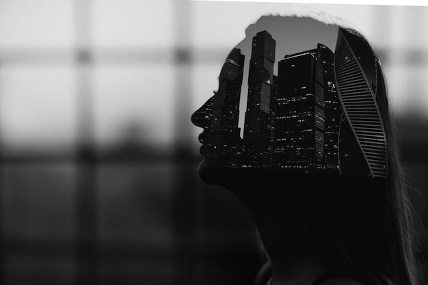 Ritratto in bianco e nero a doppia esposizione della silhouette di donna all'interno dell'edificio urbano dei grattacieli della città con grana della pellicola
