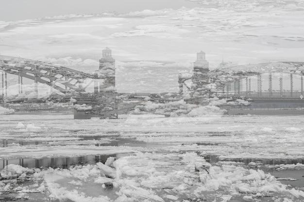 Doppia esposizione del ponte sul fiume sullo sfondo della deriva del ghiaccio. paesaggio della città di primavera con un fiume coperto di ghiaccio.