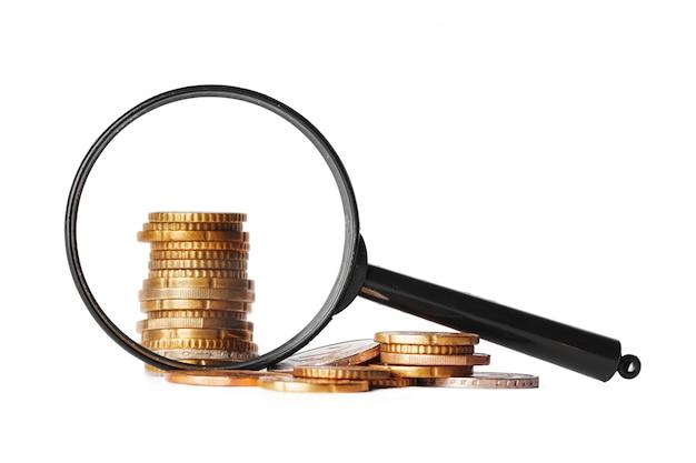 Affare di doppia esposizione con lo zoom della lente d'ingrandimento e fuoco sull'idea dei soldi delle monete per finanza