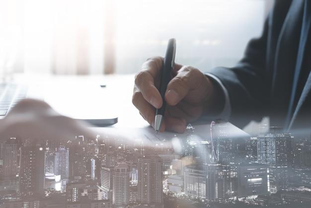 Doppia esposizione dell'uomo d'affari che firma un contratto commerciale in ufficio e in città