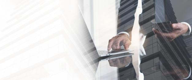Doppia esposizione di uomo d'affari che lavora su laptop e edificio per uffici per background aziendale