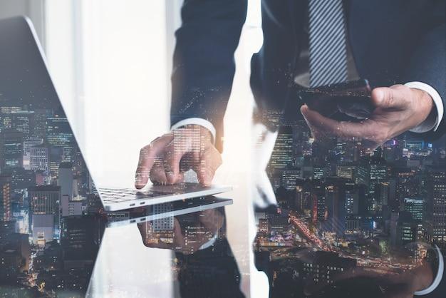 Doppia esposizione dell'uomo d'affari che lavora al computer portatile in ufficio e sullo sfondo degli affari della città