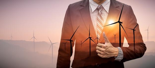 Grafica a doppia esposizione di uomini d'affari che lavorano su un parco di turbine eoliche