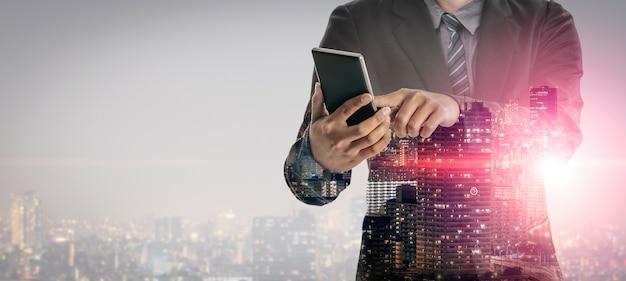 Immagine a doppia esposizione del concetto di tecnologia di rete di comunicazione aziendale - uomini d'affari che utilizzano smartphone o dispositivo di telefono cellulare sullo sfondo del paesaggio urbano moderno