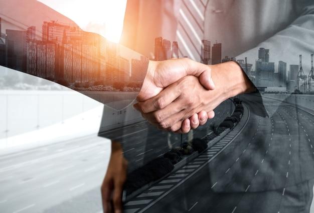 Immagine a doppia esposizione della stretta di mano di persone di affari sull'edificio per uffici della città