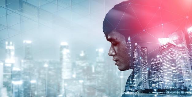Immagine a doppia esposizione di un uomo d'affari sullo sfondo della città moderna