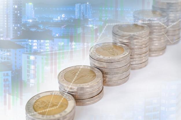 Doppia esposizione di monete impilate con grafici edilizi e candelieri.