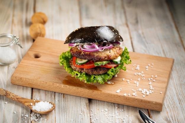 Hamburger doppio tortino nero sulla tavola di legno
