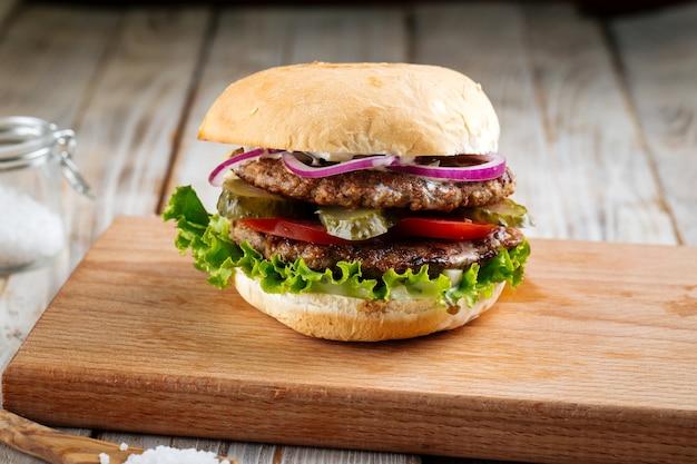 Doppio hamburger tortino con sottaceti su tavola di legno