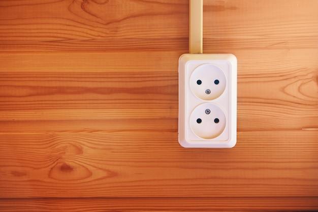 Presa elettrica a doppia alimentazione sul fondo della parete in legno. presa elettrica bianca europea montata su una parete di legno della casa di campagna. apparecchiature elettriche di casa di campagna.