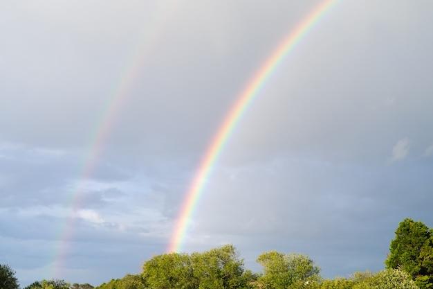 Doppio arcobaleno con sfondo di alberi cielo azzurro e nuvole. copia spazio.