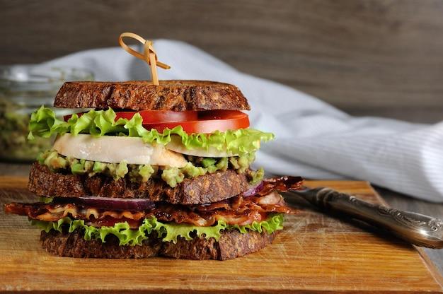 Un doppio panino di pane greco con pancetta fritta, avocado, petto di pollo e pomodori