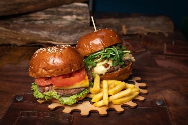 Una doppia porzione di hamburger di manzo fresco e una con noci fritte vengono servite su una parte decorativa in legno di un semplice meccanismo.