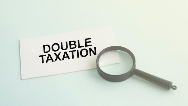 Parola di doppia tassazione su carta di carta bianca e lente di ingrandimento