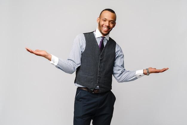 Concetto di dubbio - legame d'uso del giovane uomo d'affari afroamericano e sopra espressione grigio chiaro e confusa della parete grigio chiaro con le armi e le mani sollevate.
