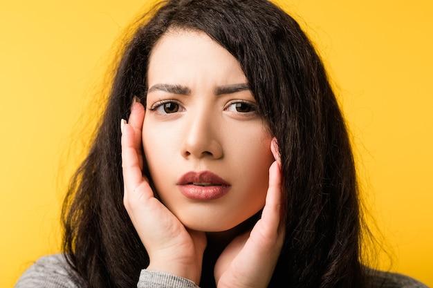 Dubbio esitazione incertezza. bella giovane donna incerta che ascolta accigliata. mani sulle guance. paura incredulità emozione.