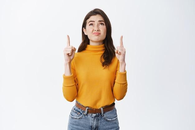 Dubbiosa e delusa donna bruna che fa una smorfia, indica e guarda qualcosa di brutto, sentendosi a disagio o turbata, in piedi sul muro bianco