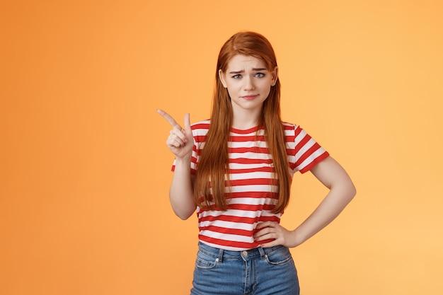 Dubbiosa ragazza rossa non crede ai tuoi discorsi sogghignando esitante esprimi incredulità non impressionata dai sospetti...